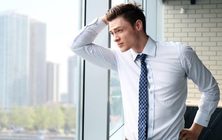 looking through window: Handsome businessman looking through window Stock Photo