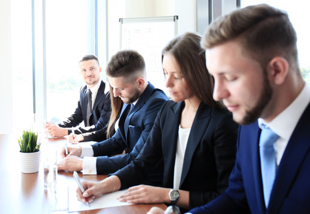 executive courses: Smiling businessman looking at camera at seminar with his colleagues near by