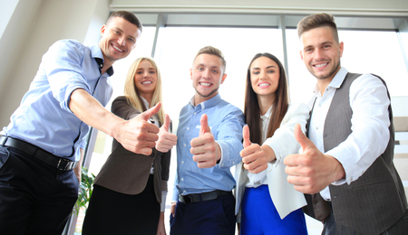 standing together: Portrait of happy businesspeople standing in office showing thumb up