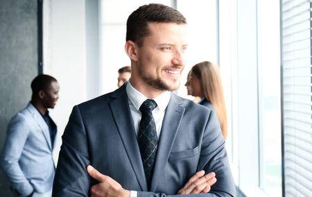 Homme d'affaires avec des collègues dans l'arrière-plan dans le bureau