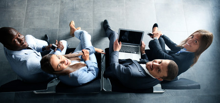 Bussinespeople grupo de jóvenes atractivas que se sientan en las sillas con un ordenador portátil, Tablet PC, teléfonos inteligentes, sonriendo Foto de archivo