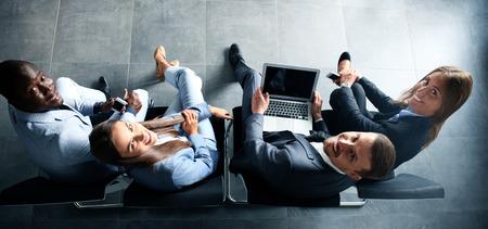 Groupe de jeunes bussinespeople attrayants assis sur les chaises en utilisant un ordinateur portable, Tablet PC, les téléphones intelligents, sourire Banque d'images