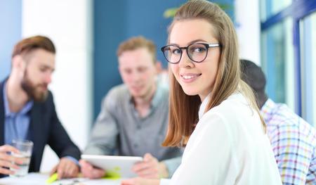 Geschäftsfrau, die mit ihren Mitarbeitern, Gruppe Menschen im Hintergrund bei modernen hellen Büro im Haus Standard-Bild