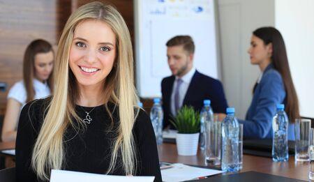 empleado de oficina: Mujer de negocios con su personal, grupo de personas en segundo plano en la oficina moderna y luminosa en el interior
