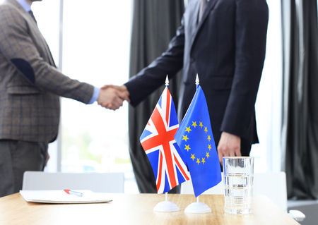 European Union and United Kingdom leaders shaking hands on a deal agreement. Brexit.
