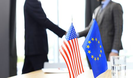 European Union and American leaders shaking hands on a deal agreement.