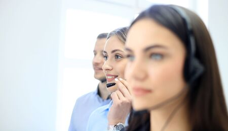 customer support: Portrait of call center worker accompanied by her team. Smiling customer support operator at work. Stock Photo