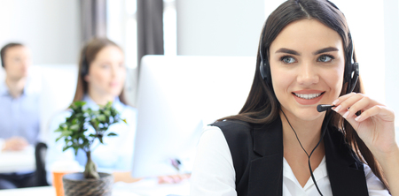 Attractive positive young businesspeople and colleagues in a call center office. Banque d'images