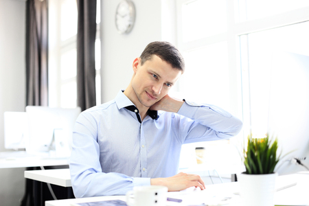 empleados trabajando: Retrato de un hombre de negocios encantado relajante en su oficina.