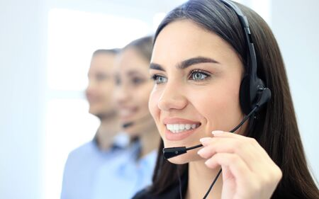 accompanied: Portrait of call center worker accompanied by her team. Smiling customer support operator at work. Stock Photo