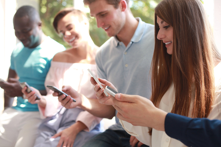 antisocial: Group of students watching smartphones. Young people addiction to new technology trends. Stock Photo