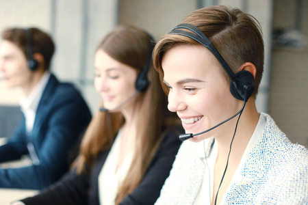 Attractive positive young businesspeople and colleagues in a call center office. Archivio Fotografico