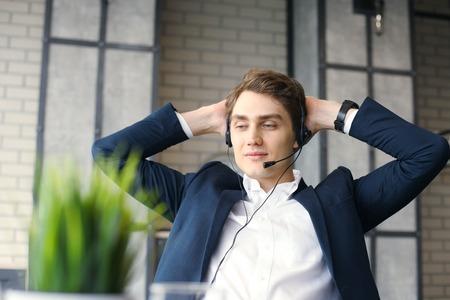 웃는 친절한 잘 생긴 젊은 남성 콜 센터 운영자.