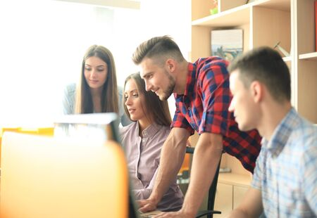 Group of young modern people in smart casual wear having a brainstorm meeting while standing in the creative office. Stock Photo