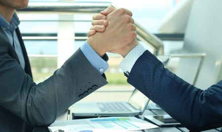 Two businessmen press hands each other on a forward background.