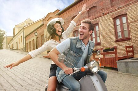 happy young couple riding scooter in town. Handsome guy and young woman travel. Adventure and vacations concept. Stock fotó