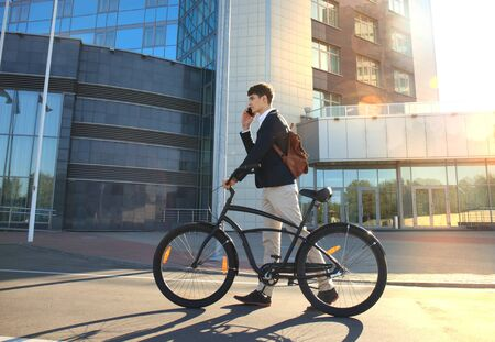 connection connections: Young businessman with bicycle and smartphone on city street