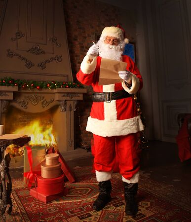 Santa Claus standing at his room at home near Christmas tree and big sack and reading Christmas letter or wish list.