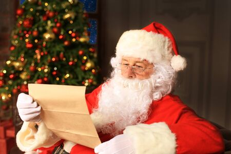 Portrait of happy Santa Claus sitting at his room at home near Christmas tree and reading Christmas letter or wish list