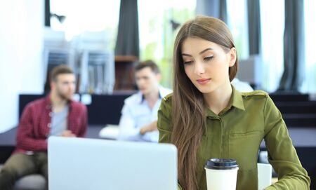 young woman smiling and typing on laptop in modern office. Stock Photo
