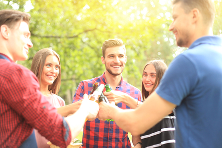 Friends toasting beer at barbecue in nature. Stock Photo