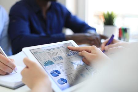 Bedrijfspersoon die financiële statistieken analyseert die op het tabletscherm worden weergegeven. Stockfoto