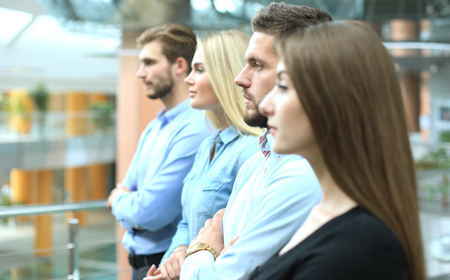 Business team standing in a row at office and looking upwards. Stock Photo