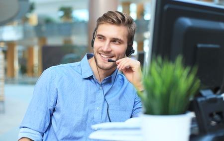 Glimlachende vriendelijke knappe jonge mannelijke call centreexploitant.