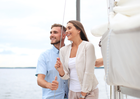 Attractive couple on a yacht enjoy bright sunny day on vacation.