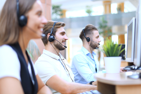 Attractive positive young businesspeople and colleagues in a call center office. Stok Fotoğraf