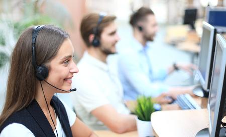 Atractivos jóvenes empresarios y colegas positivos en una oficina de centro de llamadas. Foto de archivo