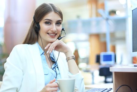 Woman customer support operator with headset and smiling. Banco de Imagens