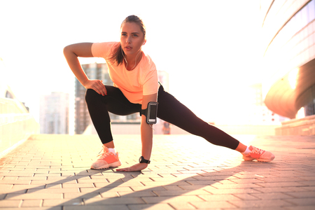 Young attractive sporty girl warming up outdoors, doing stretching in city. Imagens