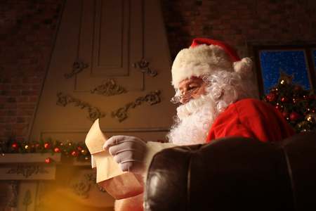 Portrait of happy Santa Claus sitting at his room at home near Christmas tree and reading Christmas letter or wish list. Stock Photo