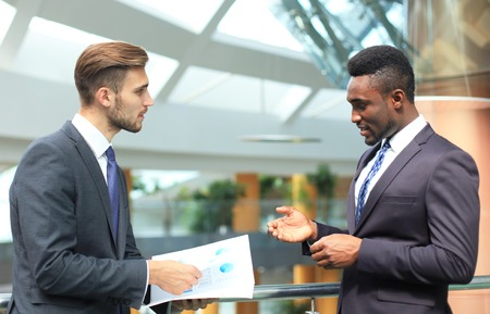 Two multinational young businessmen discussing business at meeting in office. Banque d'images