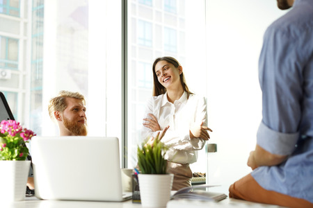 Young colleagues in smart casual wear working while spending time in the office. Stock Photo