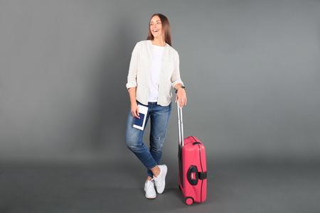 Chica joven turista en ropa casual de verano, con maleta roja, pasaporte, boletos aislados sobre fondo gris