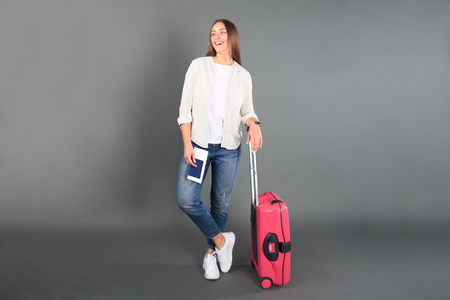 Young tourist girl in summer casual clothes, with red suitcase, passport, tickets isolated on grey background 免版税图像