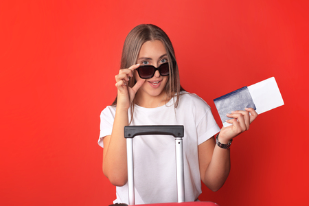 Young tourist girl in summer casual clothes, with sunglasses, red suitcase, passport isolated on red background.