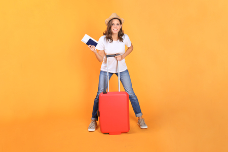 Young tourist girl in summer casual clothes, with red suitcase, passport, tickets isolated on beige background.