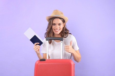 Young tourist girl in summer casual clothes, with sunglasses, red suitcase, passport isolated on purple background. Stockfoto