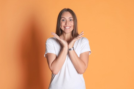 Young woman in casual clothing wondering and screaming isolated over yellow background.