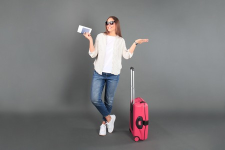 Young tourist girl in summer casual clothes, with sunglasses, red suitcase, passport, tickets isolated grey background.