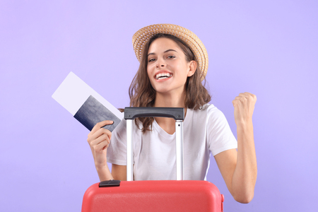 Young tourist girl in summer casual clothes, with sunglasses, red suitcase, passport isolated on purple background. Фото со стока