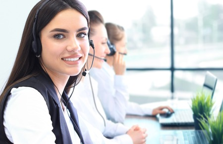 Businesswoman wearing microphone headset using computer in the office - operator, call center.