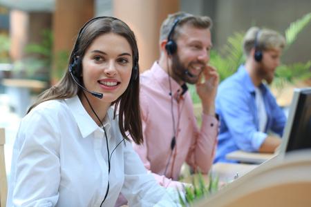 Attraenti giovani imprenditori positivi e colleghi in un ufficio del call center.
