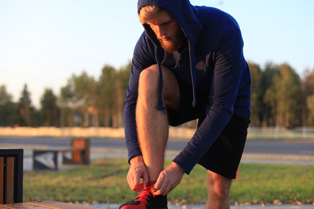 Fit athlete. Handsome adult man runner tying shoelaces at sunset or sunrise.