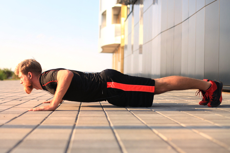 Handsome young man in sports clothing keeping plank position while exercising outdoors.