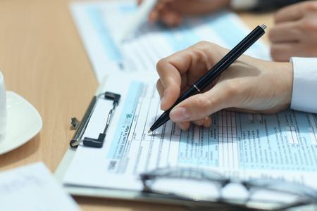 Donna che compila la dichiarazione dei redditi delle persone fisiche degli Stati Uniti, imposta 1040 al tavolo.