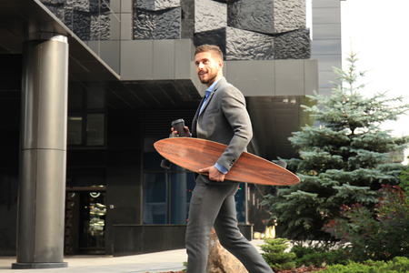 Confident young businessman walking on the street, using longboard.